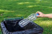 foto of throw up  - Close up hand throwing empty plastic bottle into the trash - JPG