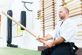 picture of aikido  - Man at Aikido martial arts with wooden sword - JPG