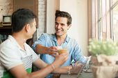 stock photo of mans-best-friend  - Two Men Cheers Toast Drink Friends Guys Happy Smile Sitting at Cafe Natural Light  - JPG
