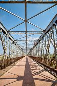 image of girder  - Old steel bridge and the reflection of its girders in bright sunlight - JPG