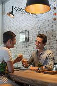 picture of mans-best-friend  - Two Men Cheers Toast Drink Ice Coffee, Asian Mix Race Friends Guys Happy Smile Sitting at Cafe Natural Light ** Note: Visible grain at 100%, best at smaller sizes - JPG