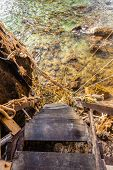 stock photo of unsafe  - an old and unsafe wooden staircase leading to the ocean with a lot of tangled ropes - JPG