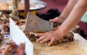 pic of spit-roast  - Butcher chopping roasted ribs with cleaver on working table - JPG