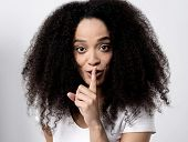 picture of silence  - Young woman making a silence gesture over white - JPG
