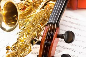 stock photo of musical scale  - Violoncello tuning pegs and shiny golden alto saxophone view on the musical notes with standard scales exercises - JPG