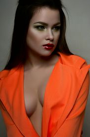 picture of big lips  - Fashion beauty female model with big breasts red lips and orange jacket - JPG