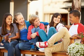 pic of pre-adolescent child  - Group Of Children Sitting On Bench In Mall - JPG