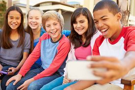 image of pre-adolescent child  - Group Of Children Sitting On Bench In Mall Taking Selfie - JPG