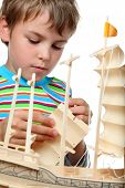 Small boy in striped shirt works with zeal on artificial ship, he makes sails