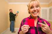 Fun Happy Couple Comparing Paint Colors in Empty Room - Woman Large, in Front, Man Smaller, Behind.