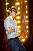 stock photo of peddlers  - young man with glass of champagne near the mirror in cabaret - JPG