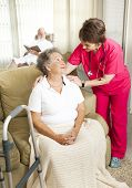 Nurse cares for an elderly woman in a nursing home.