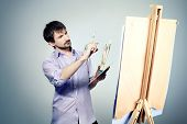 Portrait of an artist painting on easel. Shot in a studio.