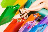 Foto de pés femininos com sacolas coloridas perto por