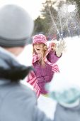 Image of attractive young woman flinging the snowball