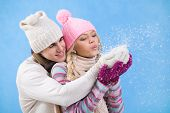 Portrait of happy young couple in warm clothes blowing snow off their palms