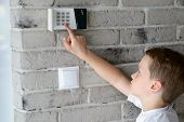 Little Baby Boy Pushes A Buttons On The Alarm Keypad poster