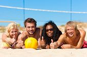 Group of friends - women and men - playing beach volleyball; they having a break and lying in the su