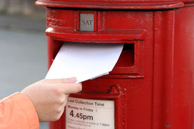 picture of post-teen  - posting letter to red british postbox on street - JPG