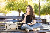 Cute Young Woman Sitting Outside In A Park Bench And Thinking While Writing In A Journal poster