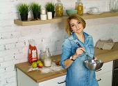 Young attractive girl prepares cookies in the kitchen. She holds a bowl and a confectionery whisk in her hands. Milk, apples, eggs and flour stand on the table