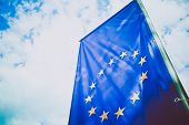 European Union Flag, Blue Sky On The Background. Blue European Union Flag With Yellow Stars In A Cir poster