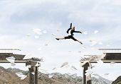 Business Woman Jumping Over Gap In Bridge Among Flying Paper Planes As Symbol Of Overcoming Challeng poster