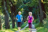 Full length front view of two active seniors with a healthy lifestyle smiling while jogging together poster