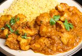 Indian chicken curry with lentils served with Bombay aloo potato curry and pilau rice.
