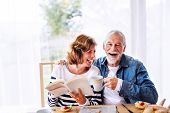 Senior Couple Eating Breakfast At Home. An Old Man And Woman Sitting At The Table, Relaxing. poster