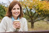 Portrait shot of an attractive, successful and happy middle aged woman female outside drinking coffe poster