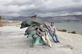Men Posing With Dolphin Monument