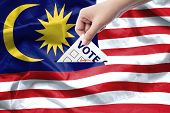 Malaysia General Election Concept. Close Up Hand Of A Person Casting A Ballot At Elections During Vo poster