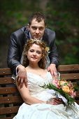 Bride sitting on the bench and groom