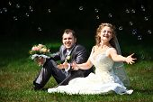 Bride and groom catching soap bubbles