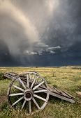 stock photo of wagon wheel  - Old Prairie Wheel Cart Saskatchewan Canada field - JPG