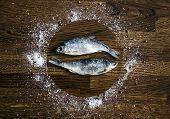 Постер, плакат: On A Wooden Background Of Small Dark Brown Discs Circle Plate Sea Salt Pepper Seasoning Coriander Pa