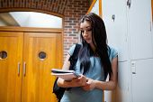 Studious young woman reading her notes in a corridor
