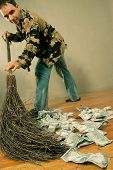 Man sweeping dollar banknotes on the wooden floor