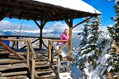 Happy Smiling Woman In Ski Clothes Drinking Tea In Open Veranda On Mountain Top With Expansive Views poster