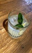 A Glass Of Lemon Mint Water And Fresh Mint Leaves On A Wooden Table poster