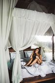 Slim Tan Woman Waking Up And Enjoying Morning Coffee In Traditional Wooden Asian Bed With White Cano poster