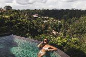 Woman In White Swimsuit And Sunglasses Relaxing In Luxury Infinity Pool With Jungle View In Ubud, Ba poster