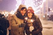 Winter Holidays. Joyful Couple Holding Bengal Lights Sparklers Celebrating New Year Outside On Centr poster
