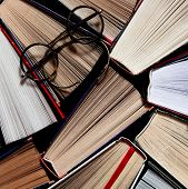 Many Multicolored Thick Open Books Stand On A Dark Background. On The Books Are Old Round Glasses poster