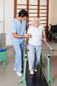 Full length portrait of a physical therapist assisting tired senior woman on walking track at hospital gym