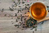 Blended Tea. Green Tea With Dry Flower Petals. Dry Leaves Of Green Tea In A Wooden Spoon And Glass C poster