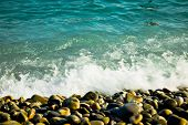 Motion Of Wave Splashed On Rounded Rocks On Beach, Motion Blur poster