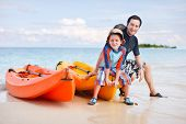 picture of kayak  - Happy father and son after kayaking relaxing near boats - JPG