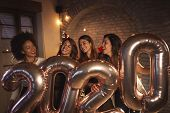 Group Of Women Having Fun Celebrating New Years Eve Together, Holding Giant Balloons Shaped As Numbe poster